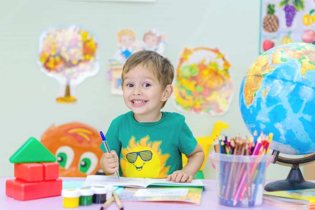 toddler holding a pen and smiling