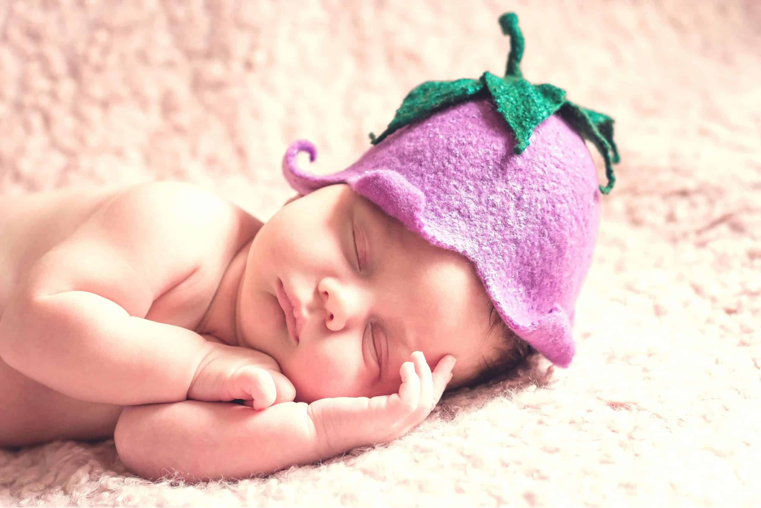 newborn baby with an eggplant hat | saving for baby