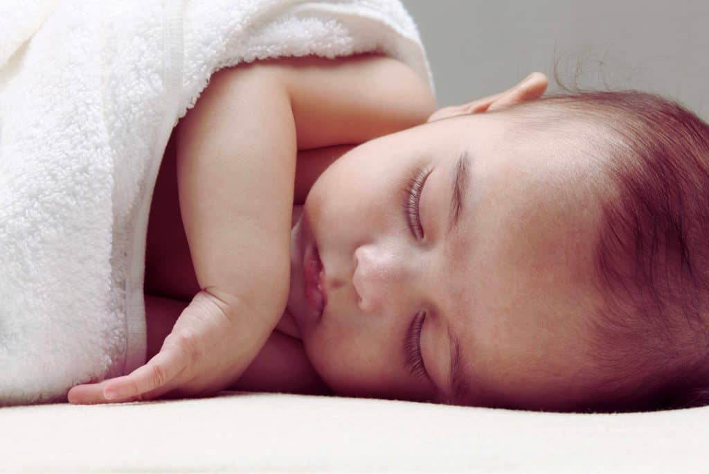 baby sleeping sideways covered in a white towel